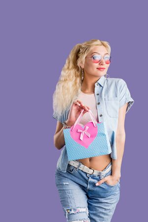 Portrait of a happy beautiful blonde girl wearing jeans, denim shirt, top and stylish sunglasses holding small shopping or gift bag isolated over violet background. Shopping, sale, holiday concept.