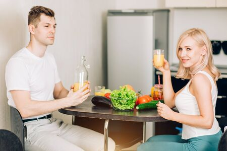 Young attractive relaxed couple having breakfast sitting at kitchen table, enjoying fresh organic food at home together, smiling looking at camera. Healthy eating and lifestyle concept.