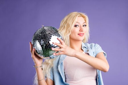 Studio portrait of beautiful stylish lovely blonde long haired woman posing with shining disco ball, dressed in fashionable clothes isolated on purple background. Party, lifestyle concept.