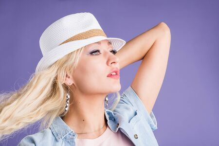 Head shot of elegant blonde female with clean skin, makeup wearing straw hat, denim shirt, stylish earrings enjoying sunny warm summer day on vacation looking to side on lilac background. Stock Photo