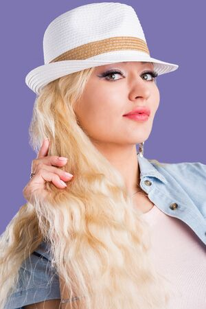 Head shot of confident happy charming blonde girl with clean skin, long eyelashes, makeup, enjoying summer vacation smiling wearing stylish straw hat and gazing to side over purple background. Close up.