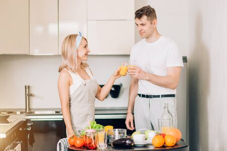 Happy young couple making organic beverage in kitchen together, is clinking glasses, drinking freshly squeezed orange juice in kitchen, celebrating husbands success at work. Healthy lifestyle concept.