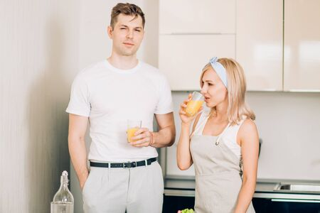 Young happy couple in love drinking fresh juice while standing in the kitchen talking, looking and smiling at each other. Close up horizontal shot. Healthy lifestyle concept. Stok Fotoğraf