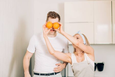 Cheerful young couple having fun in modern kitchen while cooking together, making fresh fruit juice. Joyful blonde Caucasian woman covering eyes her boyfriend with oranges. Stok Fotoğraf