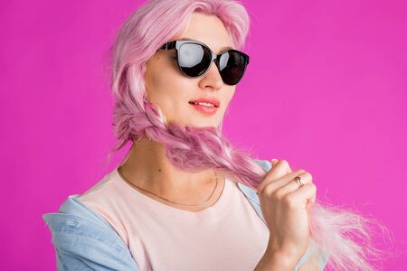 Closeup indoor shot of caucasian woman with pink braid wearing sunglasses, earrings pale pink t shirt looking at camera with open mouth on coral background. Summer, beauty, hair dye, cosmetics concept