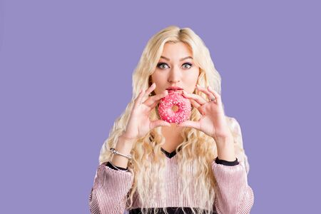 Joyful caucasian blonde woman having delicious pastry, holding pink sweet glazed doughnut, enjoying tasty dessert isolated against purple blue background. Holiday, unhealthy food, nutrition concept.
