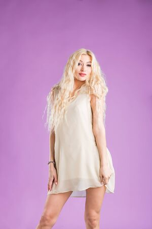 Portrait of graceful caucasian woman posing in white summer dress. Indoor photo of lovely smiling girl with blonde long wavy hair isolated on purple background.