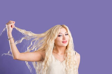 Relaxing pleased dreamy caucasian blonde woman with long wavy hair, beautiful makeup wearing dress, bracelets, touching head looking down with smile isolated on violet background. Close up studio shot