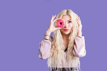 Charming girl with long wavy blonde hair positively posing, holding fresh pink donut on purple background. Portrait of attractive young woman wearing dress having fun with sweet doughnut. Фото со стока