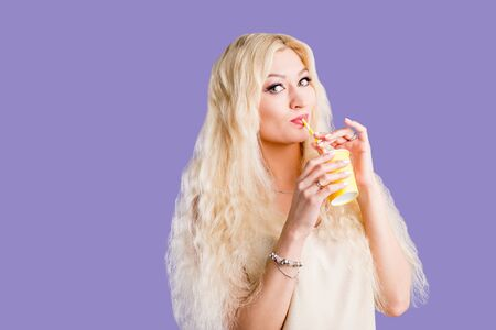 Attractive young caucasian woman with long blonde hair, holding takeaway yellow paper cup, drinking soda with straw, enjoying tasty beverage with closed eyes , posing against violet background.
