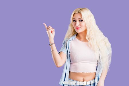 Young attractive cute blonde woman in stylish clothes smiling looking at camera and pointing left with index finger, standing over violet background with copy space. Female model advertising product.