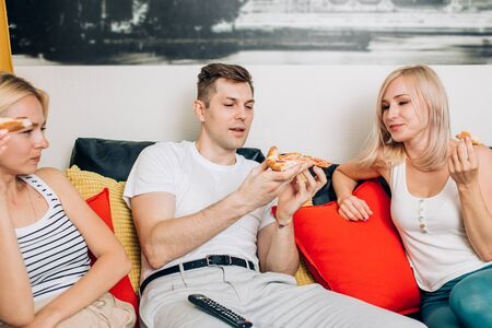 Group of cheerful young friends in casual clothes eating pizza, sitting on couch and having fun in living room at home. Weekend, leisure, relaxation, fast food concept.