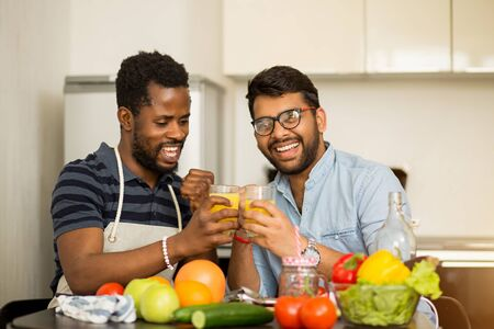 Yes We did it Two multi ethnic male friends clenching fists in triumph, holding glasses with fresh juice, sitting in kitchen smiling looking at camera. People, victory, cooking concept. Stock fotó