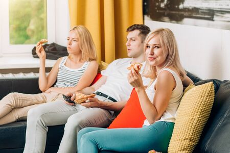 Group of young friends eating pizza and watching tv, spending time together at home in weekend. Home party. Fast food, relaxation concept. Selective focus.