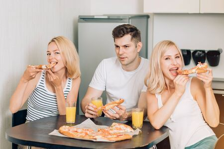 Three caucasian happy students eating pizza, drinking orange juice in kitchen. Friends having party at home, talking, laughing and having fun. Friendship, students, weekend concept.