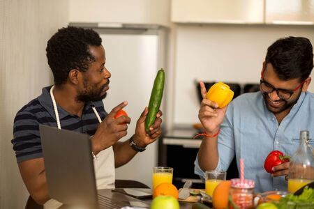 Handsome african american young man and his indian friend sitting at table holding vegetables, discussing recipe, looking at each other, using laptop in kitchen. People, communication, cooking concept