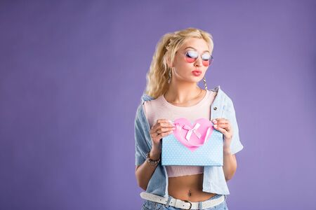 Beautiful stylish interested blonde woman wearing denim shirt, pink t shirt, sunglasses, jewellery looking inside shopping bags, opening present on violet background. Sale, gift, holiday concept.