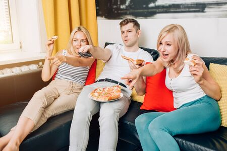 Group of young friends eating pizza and watching tv, spending time together at home in weekend. Home party. Fast food concept. Students relaxing after study. Stock Photo