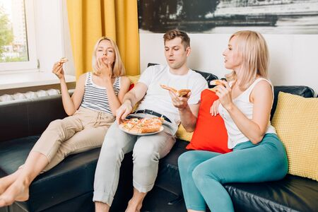 Young people in casual clothes eating pizza, sitting on sofa, talking, watching TV while resting at home. Weekend, leisure, unhealthy food concept. Stock Photo