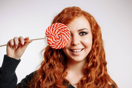 Beautiful young curly redhead surprised girl holding a red white lollipop on white background. A woman with mouth open and closes the eye candy. human emotions, expressive facial expressions
