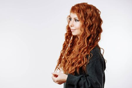 Caucasian female with red curly shiny hair looking away with smile. Indoor close up photo of attractive woman isolated on white background with copy space.