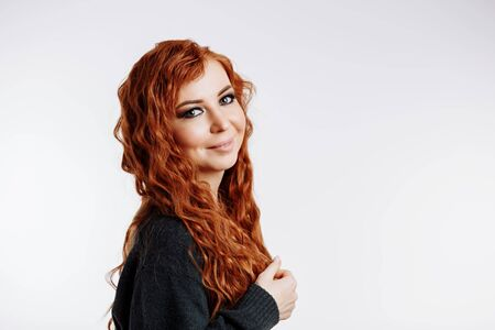 Cheerful wavy redhead woman with clean skin, green eyes, wearing black sweater smiling looking at camera posing over white background with copy space.