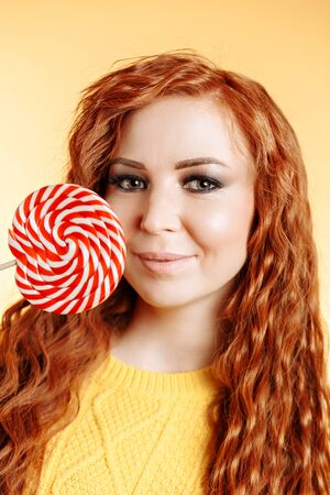 Beautiful curly redhead woman holding a red white lollipop looking at the camera and smiling. Pretty young girl wearing a yellow sweater, on orange background with copy space in the Studio.