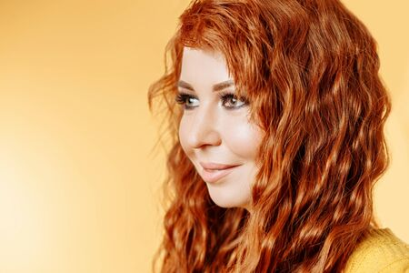 Closeup portrait of happy redhead woman looking away with smile on yellow background with copy space
