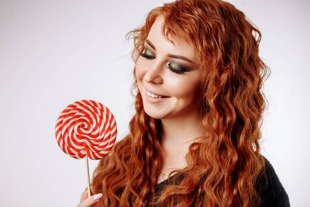 Beautiful young girl holding a red white lollipop and smiling. Pretty happy curly redhead woman looking at lollipop on white background. Фото со стока - 129914247