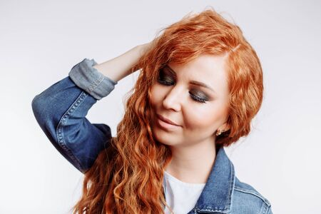 Enchanting ginger woman in casually white t shirt and denim jacket standing on light background. Romantic young woman with trendy curly hairstyle, smiling. Makeup, beauty, happiness, positive emotions Stock Photo