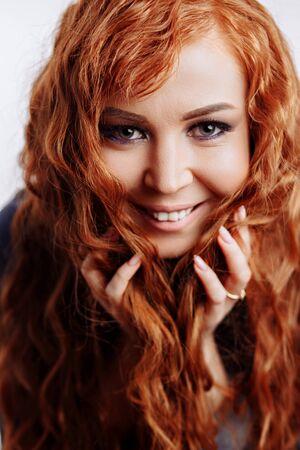 Chica pelirroja hermosa atractiva alegre feliz sonriendo mirando a cámara tocando su pelo largo y rizado sobre fondo blanco. Expresiones faciales expresivas, peinado, concepto de cuidado del cabello.
