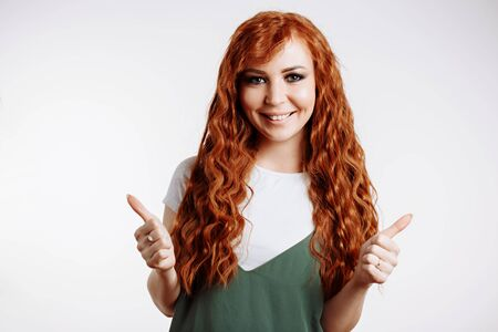 I like it Happy young caucasian female with long red curly hair giving thumbs up and smiling cheerfully, showing her support to someone. Body language, good luck, positive emotions concept.