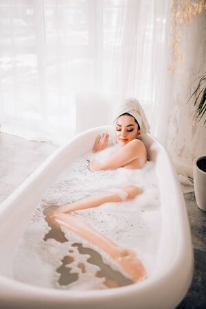 Overhead portrait of sensual caucasian woman taking bath in weekend. Indoor shot of blissful naked lady lying in bathtub near window and enjoying time for herself. Perfect healthy skin, spa, body care