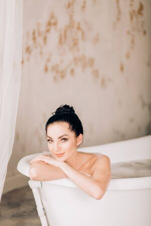 Young pretty black haired woman smiling, thinking about something pleasant while taking bath. Close up portrait of sensual beautiful female model relaxing in bathtub. Skin and body care, spa concept. Stok Fotoğraf