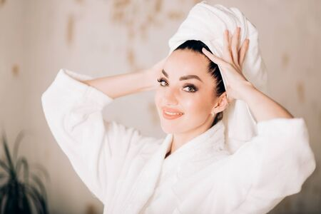 Close up portrait of beautiful young caucasian woman with beautiful eyes and healthy clean skin after spa treatments wearing towel on head and bathrobe, looking smiling at camera. Cosmetics products.