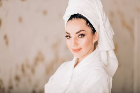 Closeup of beautiful woman with long eyelashes and healthy fresh perfect skin, makeup, dressed in bathrobe and towel on head. Beauty salon,cosmetic products, skin care and spa treatment concept.