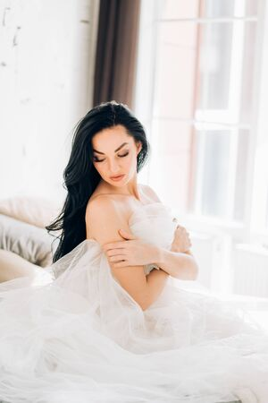 Portrait of beautiful sensual naked bride in white veil sitting on bed in wedding morning at home, looking down with dreamy expression. Close up of elegant model with long hair and makeup indoor. Banque d'images - 131309709