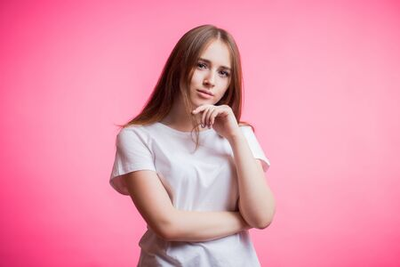 Portrait of happy ginger girl wears a white shirt and smiling looking at camera on a pink background with a copy space. Human emotions, facial expression, joy, happiness concept