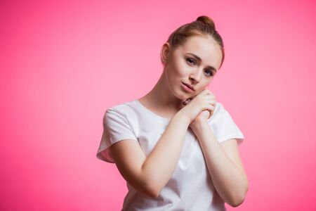 Dreamy sensual cute girl in white t-shirt with smile looking at camera on pink background. Human emotions, facial expression concept