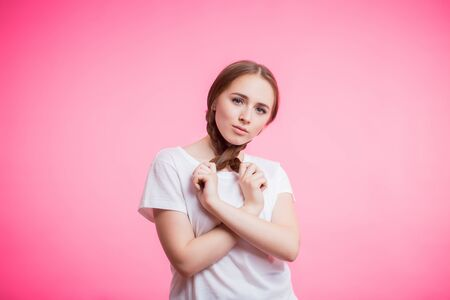 Beautiful portrait of young student girl with pigtails and white t-shirt on pink background with copy space. Human emotions, facial expression concept