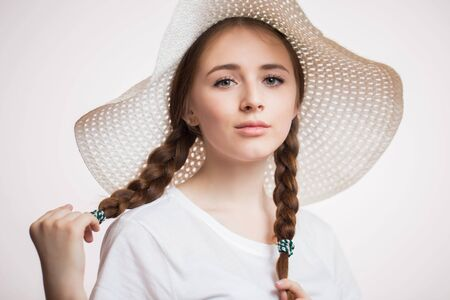Head shot portrait of ginger smiling woman in summer beige hat looking at camera. Teenager girl with braids, close up