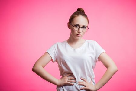 Horizontal portrait of beautiful woman wearing her red hair in bun on a pink background. Young student girl with glasses and white t-shirt looking at camera