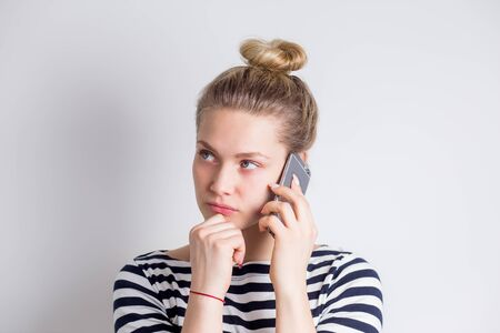 Dissatisfied frustrated young business woman talking on a smartphone over white background. Unsuccessful negotiations, bad news, conversations, bad mood concept Stockfoto