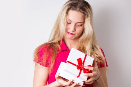 Sad beautiful blonde woman dissatisfied with the gift. Bad gift, negative emotions