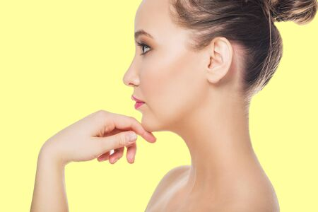 beautiful young woman on yellow background. Spa, clean skin, care and cosmetics concept Фото со стока