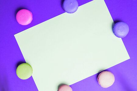 Closeup paper for copy space, text and advertising on purple background with multicolored pink and yellow macaroons. Frame and form for copy space Zdjęcie Seryjne
