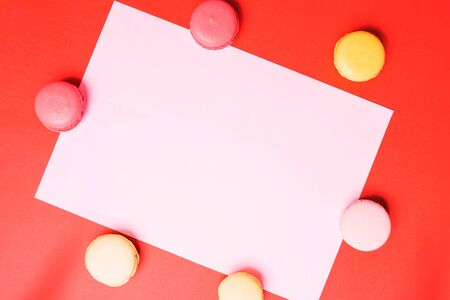 Closeup paper for copy space, text and advertising on red background with multicolored pink and yellow macaroons