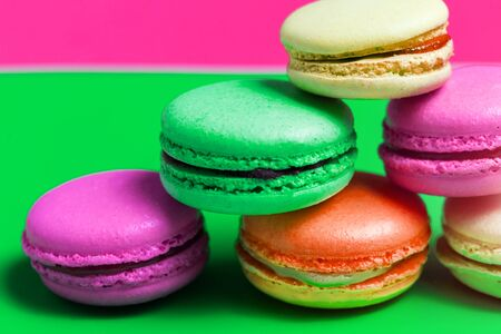 Closeup of colorful pink, orange, green. beige French sweet macaroons on the table. Macro photo cakes Banco de Imagens
