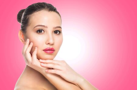 Beauty spa woman with perfect skin portrait. Beautiful brunette spa girl on pink background, close up, copy space. Skin care, youth, make up concept