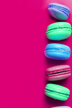 Multicolored baked macaroons on a pink background with copy space, closeup Banco de Imagens